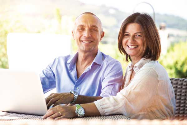 middle aged couple outside on a laptop computer