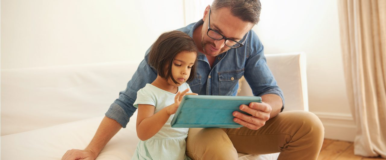 Man wearing glasses helping dark haired young girl use tablet