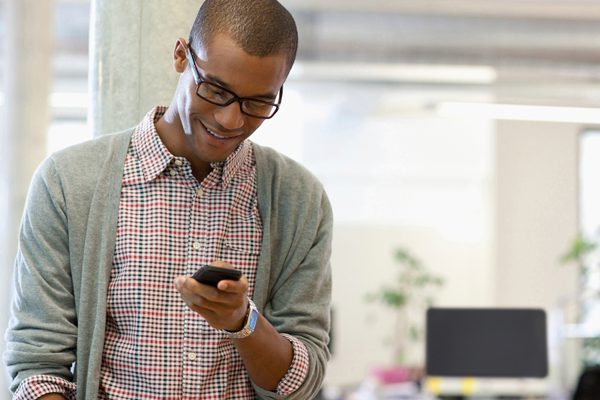 Man wearing glasses, plaid button down shirt, and cardigan while smiling looking at his mobile phone