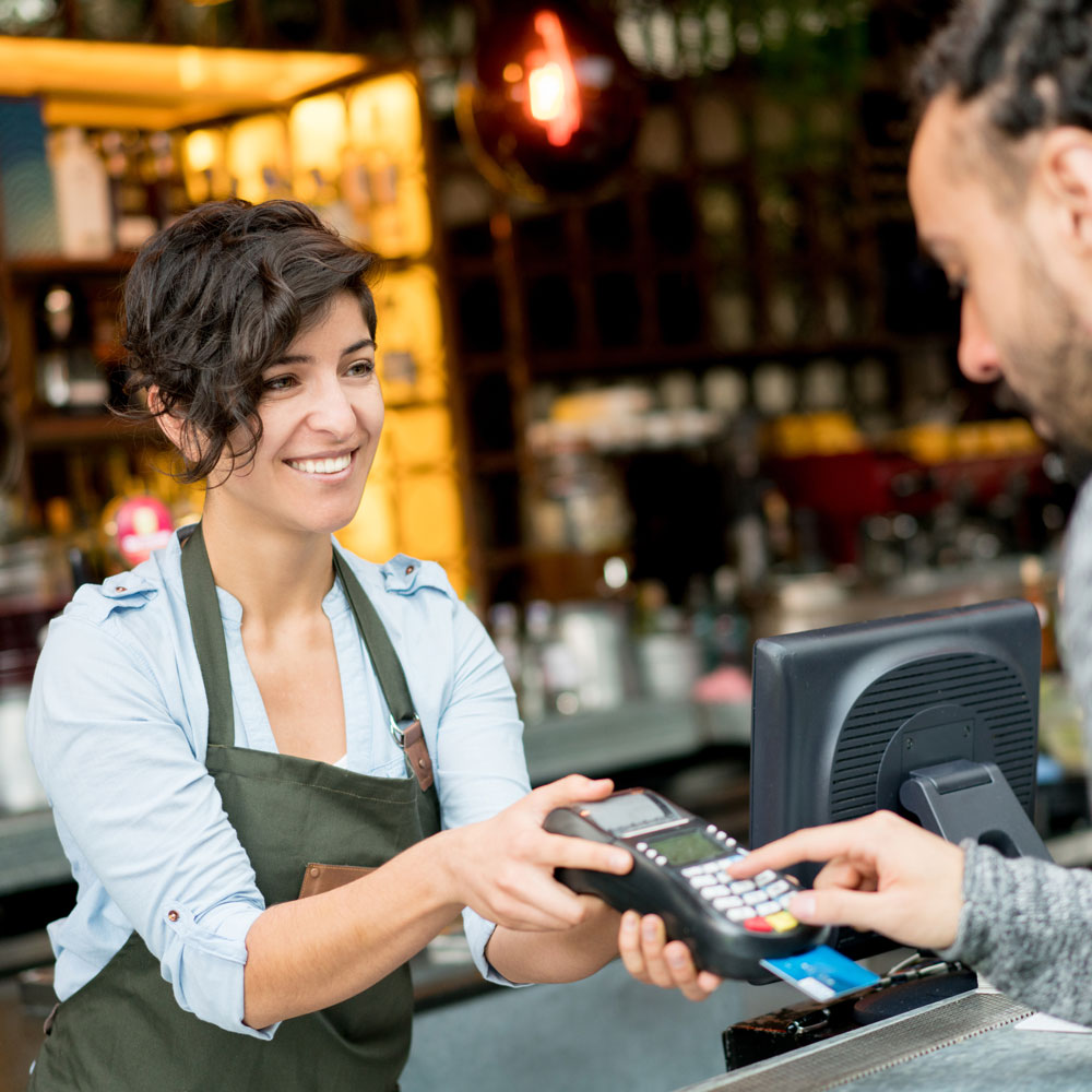 Women wearing a utility apron holds credit card machine at a store while man presses keypad