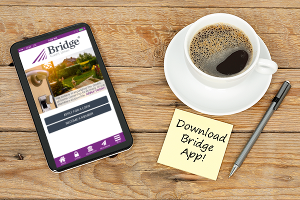 An electronic tablet showing the Bridge app, a cup of coffee on a saucer, a pen, and a paper note pad laying on a wooden background