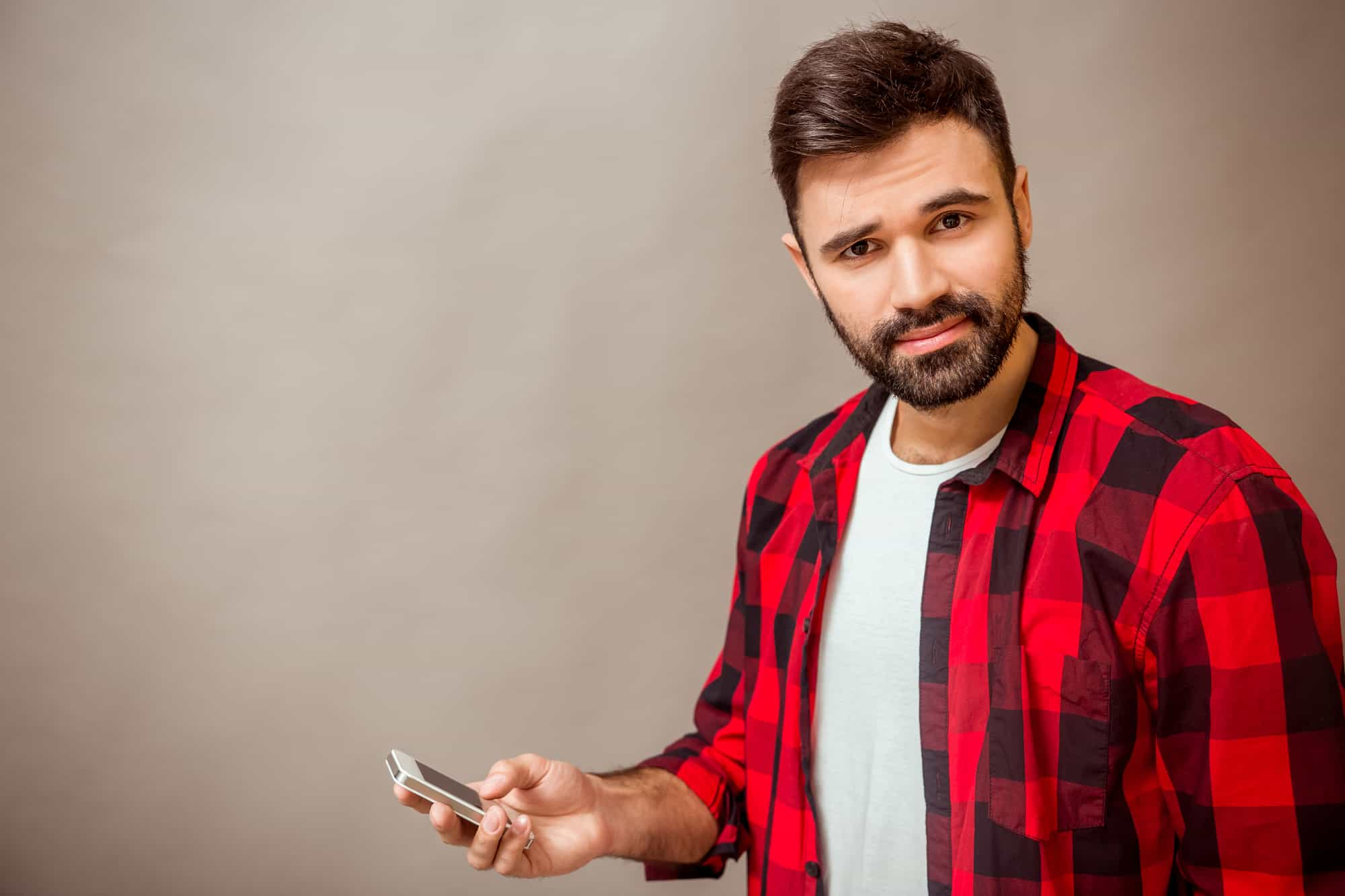 Beautiful young man in a checkered shirt, smartphone in hand, expressing