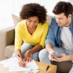 couple with papers and calculator at home