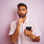 Young indian man using smartphone standing over isolated pink background serious face thinking about question, very confused idea